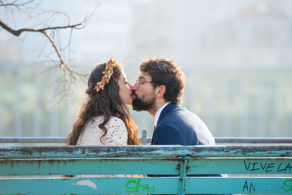 Couple kissing on a bench with girl wearing flower crown