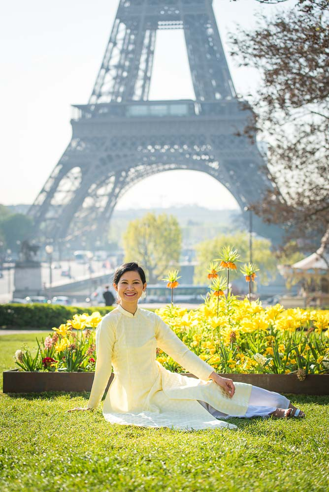 Portrait of girl sitting on grass in from of Eiffel tower