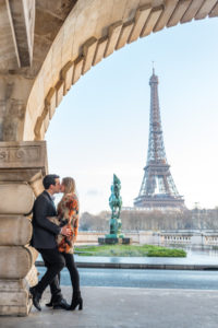 Couple kissing under bridge in Paris with Eiffel tower