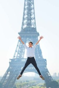 Kid jumping in front of the Eiffel Tower in paris