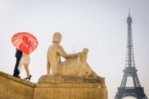 Couple with red umbrella at Eiffel Tower